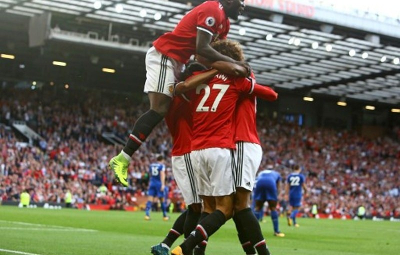 Manchester United's Belgian midfielder Marouane Fellaini celebrates with teammates after scoring their second goal during the English Premier League football match between Manchester United and Leicester City at Old Trafford in Manchester, north west England, on August 26, 2017. / AFP PHOTO / Geoff CADDICK / RESTRICTED TO EDITORIAL USE. No use with unauthorized audio, video, data, fixture lists, club/league logos or 'live' services. Online in-match use limited to 75 images, no video emulation. No use in betting, games or single club/league/player publications.  /