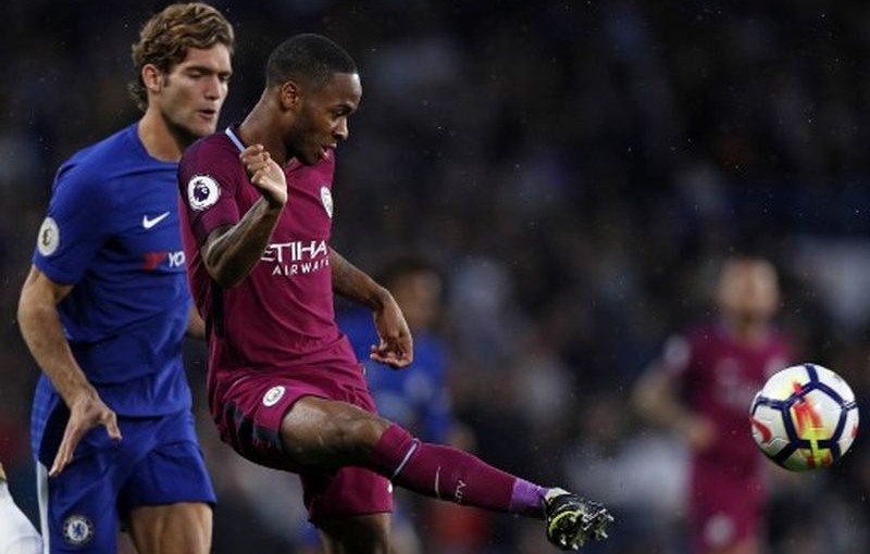 Manchester City's English midfielder Raheem Sterling (R) passes the ball during the English Premier League football match between Chelsea and Manchester City at Stamford Bridge in London on September 30, 2017. / AFP PHOTO / Adrian DENNIS / RESTRICTED TO EDITORIAL USE. No use with unauthorized audio, video, data, fixture lists, club/league logos or 'live' services. Online in-match use limited to 75 images, no video emulation. No use in betting, games or single club/league/player publications.  /