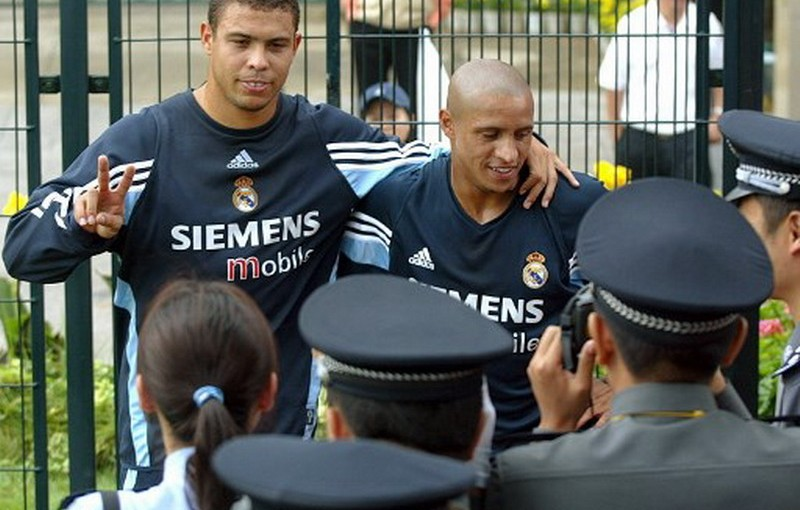 Brazilian football star Ronaldo (L) and Roberto Carlos (R) pose for photographs as Chinese police take pictures as players move to the neighbouring field during the Real Madrid's morning practice session at Hongta sports center in the southwestern city of Kunming, 29 July 2003. AFP PHOTO/LIU Jin / AFP PHOTO / LIU JIN